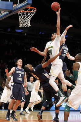 NEW YORK, NY - APRIL  02:  Isaiah Austin #21 of the Baylor Bears puts up a shot against Brandon Davies #0 and teammate Nate Austin #33 of the Brigham Young Cougars in the first half during the 2013 NIT Championship - Semifinals at the Madison Square Garde