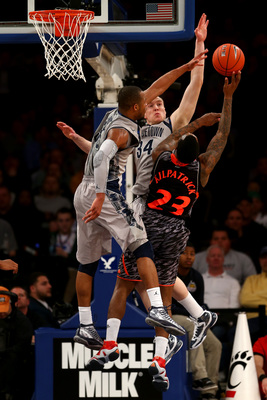 NEW YORK, NY - MARCH 14:  Sean Kilpatrick #23 of the Cincinnati Bearcats drives for a shot attempt in the second half against Jabril Trawick #55 and Nate Lubick #34 of the Georgetown Hoyas during the quaterfinals of the Big East Men's Basketball Tournamen
