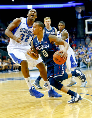 Feb 10, 2013; Newark, NJ, USA;  Connecticut Huskies guard Shabazz Napier (13) gets around Seton Hall Pirates center Kevin Johnson (32) during the first half at the Prudential Center. Connecticut Huskies defeat the Seton Hall Pirates 78-67. Mandatory Credi