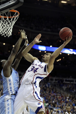 KANSAS CITY, MO - MARCH 24: Perry Ellis #34 of the Kansas Jayhawks shoots over P.J. Hairston #15 of the North Carolina Tar Heelsin the during the third round of the 2013 NCAA Men's Basketball Tournament at the Sprint Center on March 24, 2013 in Kansas Cit