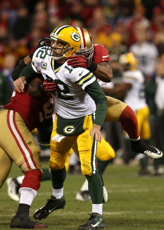 SAN FRANCISCO, CA - JANUARY 12:  Outside linebacker Ahmad Brooks #55 of the San Francisco 49ers tackles quarterback Aaron Rodgers #12 of the Green Bay Packers after throwing the ball during the NFC Divisional Playoff Game at Candlestick Park on January 12