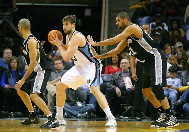 Marc Gasol backing down Tim Duncan with Tony Parker looking on in a Grizzlies versus Spurs 2013 regular season matchup in Memphis.