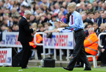 NEWCASTLE UPON TYNE, ENGLAND - MAY 19:  Managers Arsene Wenger (R) of Arsenal encourages his players as Alan Pardew of Newcastle walks back to his seat during the Barclays Premier League match between Newcastle United and Arsenal at St James' Park on May