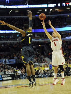 Mar 15, 2013; Chicago, IL, USA; Wisconsin Badgers guard Ben Brust (1) shoots over Michigan Wolverines forward Glenn Robinson III (1)  in the second half during the quarterfinals of the Big Ten tournament at the United Center. Mandatory Credit: David Banks