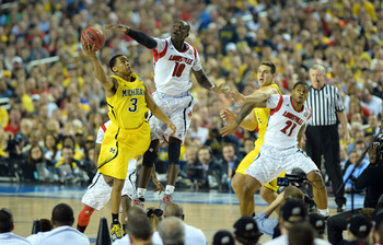 Apr 8, 2013; Atlanta, GA, USA; Michigan Wolverines guard Trey Burke (3) shoots against the Louisville Cardinals center Gorgui Dieng (10) during the first half of the championship game in the 2013 NCAA mens Final Four at the Georgia Dome.  Mandatory Credit