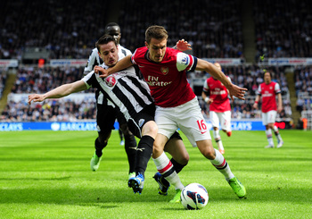NEWCASTLE UPON TYNE, ENGLAND - MAY 19:  Mathieu Debuchy of Newcastle in action against Aaron Ramsey of Arsenal during the Barclays Premier League match between Newcastle United and Arsenal at St James' Park on May 19, 2013 in Newcastle upon Tyne, England.