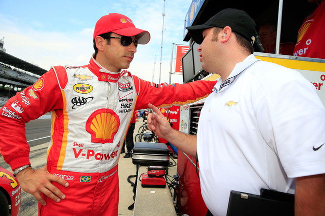 INDIANAPOLIS, IN - MAY 17:  Helio Castroneves of Brazil, driver of the #3 Shell V-Power/Penzoil Ultra Team Penske Chevrolet, talks with crew members during practice for the 2013 Indianapolis 500 at Indianapolis Motor Speedway on May 17, 2013 in Indianapol