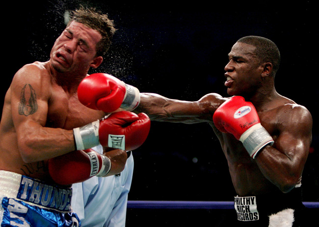 ATLANTIC CITY, NJ - JUNE 25:  Arturo Gatti (L) is hit by Floyd Mayweather Jr. (R) during their WBC Super Lightweight Championship fight at Boardwalk Hall on June 25, 2005 in Atlantic City, New Jersey.  Mayweather won the fight after Gatti's corner stopped