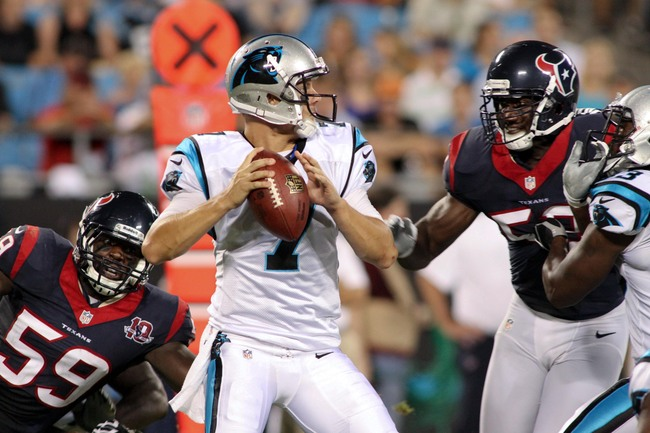 Aug 11, 2012; Charlotte, NC, USA Carolina Panthers quarterback Jimmy Clausen (7) gets pressured by Houston Texans linebacker Whitney Mercilus (59) during the second half at Bank of America Stadium. The Texans defeated the Panthers 26-13. Mandatory Credit: