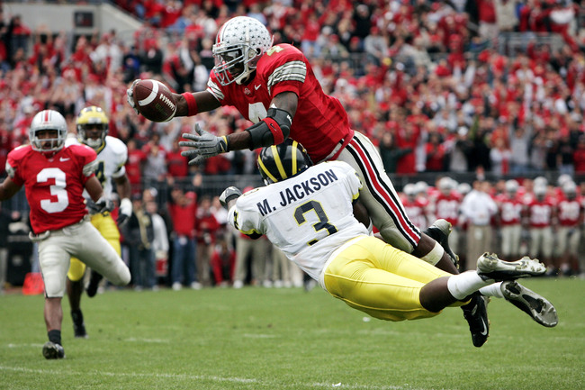 COLUMBUS, OH - NOVEMBER 20:  Wide receiver Santonio Holmes #4 of the Ohio State Buckeyes dives into the end zone for a touchdown over cornerback Marlin Jackson #3 of the Michigan Wolverines during the third quarter on November 20, 2004 at Ohio Stadium in