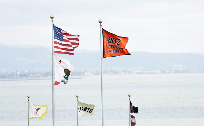 SAN FRANCISCO, CA - APRIL 05:  The 2012 Championship Banner flies next to the American Flag before the San Francisco Giants home opener against the St. Louis Cardinals at AT&T Park on April 5, 2013 in San Francisco, California.  (Photo by Ezra Shaw/Getty