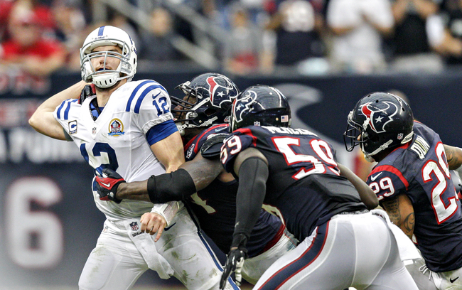 HOUSTON, TX - DECEMBER 16: Andrew Luck #12 of the Indianapolis Colts gets rid of the ball as he is tackled by Antonio Smith #94 of the Houston Texans in the second half at Reliant Stadium on December 16, 2012 in Houston, Texas. Texans win 29-17 to clinch