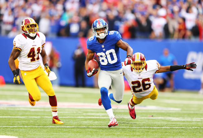 EAST RUTHERFORD, NJ - OCTOBER 21:  Victor Cruz #80 of the New York Giants runs after a catch for the winning touchdown as  Madieu Williams #41, and  Josh Wilson #26 of the Washington Redskins give chase in the fourth quarter of a 27-23 Giant win  at MetLi