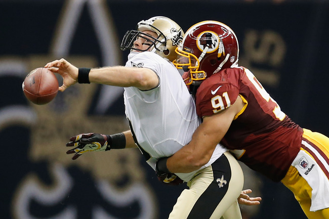 NEW ORLEANS, LA - SEPTEMBER 09:   Drew Brees #9 of the New Orleans Saints throws the ball as he is tackled by  Ryan Kerrigan #91 of the Washington Redskins  during the season opener at Mercedes-Benz Superdome on September 9, 2012 in New Orleans, Louisiana