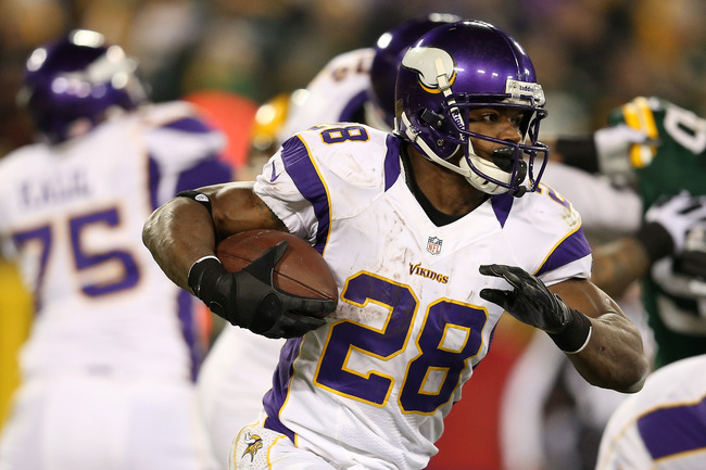GREEN BAY, WI - JANUARY 05:  Running back Adrian Peterson #28 of the Minnesota Vikings runs the ball against the Green Bay Packers during the NFC Wild Card Playoff game at Lambeau Field on January 5, 2013 in Green Bay, Wisconsin.  (Photo by Andy Lyons/Get