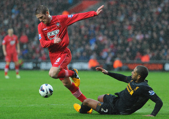 Taking it lying down: Glen Johnson watches as Craig Gardner skips passed him.