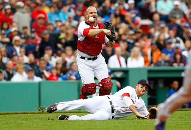 BOSTON, MA - MAY 11: David Ross #3 of the Boston Red Sox throws a bunted ball over teammate Will Middlebrooks #16 of the Boston Red Sox during the game on May 11, 2013 at Fenway Park in Boston, Massachusetts. (Photo by Jared Wickerham/Getty Images)