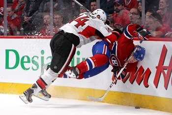 Ottawa Senator Colin Greening takes Prust hard into the boards.