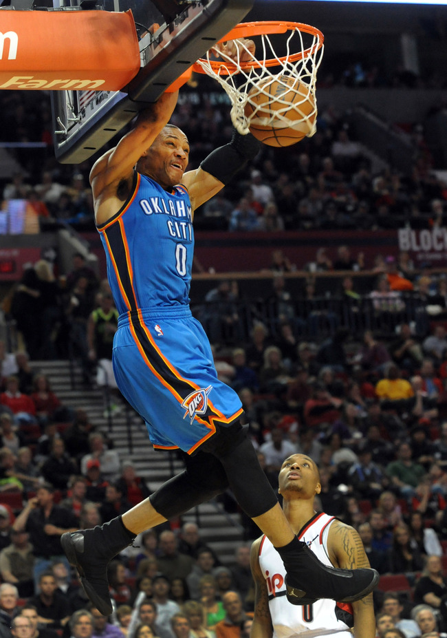 April 12, 2013; Portland, OR, USA; Oklahoma City Thunder point guard Russell Westbrook (0) dunks the ball as Portland Trail Blazers point guard Damian Lillard (0) looks on during the third quarter of the game at the Rose Garden. The Thunder won the game 1