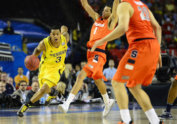 Apr 6, 2013; Atlanta, GA, USA; Michigan Wolverines guard Trey Burke (3) dribbles as Syracuse Orange guards Michael Carter-Williams (1) and Brandon Triche (20) defend in the second half of the semifinals during the 2013 NCAA mens Final Four at the Georgia