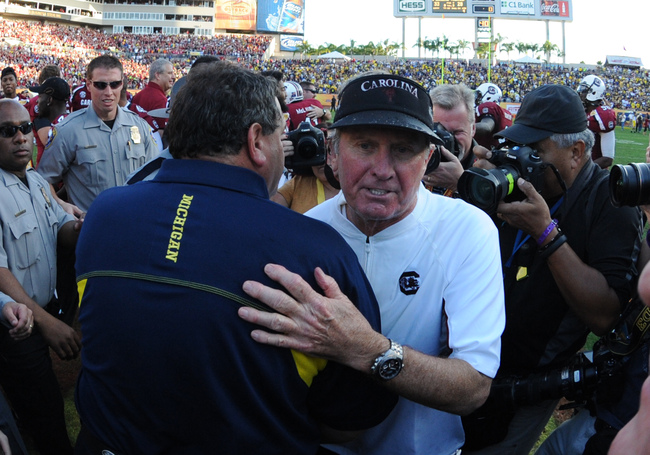 TAMPA, FL - JANUARY 01:  Coach Steve Spurrier of the South Carolina Gamecocks greets coach Brady Hoke of the Michigan Wolverines after play in the Outback Bowl January 1, 2013 at Raymond James Stadium in Tampa, Florida.  South Carolina won 33 - 28. (Photo