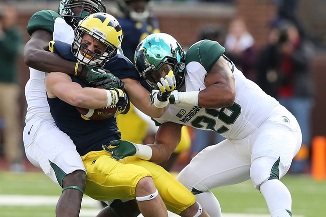 ANN ARBOR, MI - OCTOBER 20: Drew Dileo #9 of the Michigan Wolverines catches a pass from Denard Robinson #16 and runs for a 35-yard gain as Kurtis Drummond #27 and Darqueze Dennard #31 of the Michigan State Spartans make the stop during the second quarter