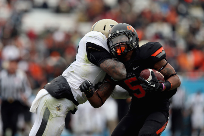 DALLAS, TX - JANUARY 01:  Josh Stewart #5 of the Oklahoma State Cowboys is tackled by Josh Johnson #28 of the Purdue Boilermakers during the Heart of Dallas Bowl at Cotton Bowl on January 1, 2013 in Dallas, Texas.  (Photo by Ronald Martinez/Getty Images)
