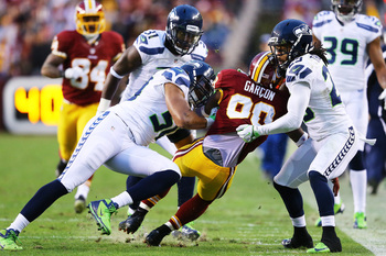LANDOVER, MD - JANUARY 06:   Pierre Garcon #88 of the Washington Redskins is tackled by  Bruce Irvin #51 and  Earl Thomas #29 of the Seattle Seahawks in the first quarter of the NFC Wild Card Playoff Game at FedExField on January 6, 2013 in Landover, Mary