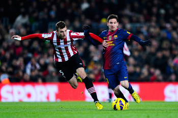 Amorebieta (left) jostles with Messi