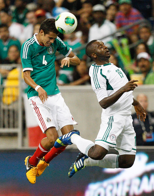 HOUSTON - MAY 31:  Diego Reyes #4 of Mexico heads the ball away from Sunday Mba #19 of Nigeria in the second half at Reliant Stadium on May 31, 2013 in Houston, Texas.  (Photo by Bob Levey/Getty Images)