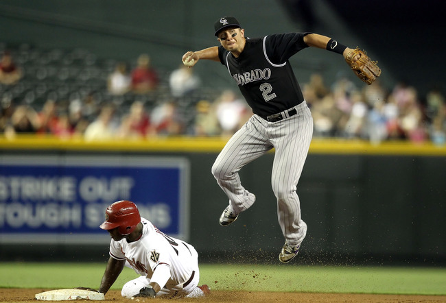 PHOENIX, AZ - AUGUST 29:  Infielder Troy Tulowitzki #2 of the Colorado Rockies throws over the sliding Justin Upton #10 of the Arizona Diamondbacks to complete a double play during the third inning of the Major League Baseball game at Chase Field on Augus