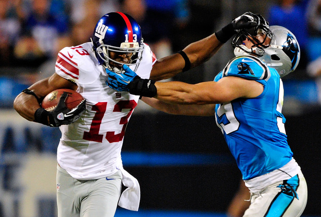 CHARLOTTE, NC - SEPTEMBER 20:  Ramses Barden #13 of the New York Giants stiff-arms Luke Kuechly #59 of the Carolina Panthers during play at Bank of America Stadium on September 20, 2012 in Charlotte, North Carolina.  (Photo by Grant Halverson/Getty Images