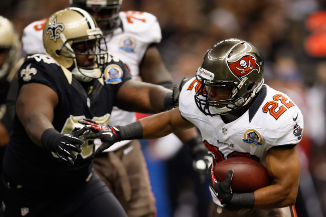 NEW ORLEANS, LA - DECEMBER 16:   Doug Martin #22 of the Tampa Bay Buccaneers runs past   Sedrick Ellis #98 of the New Orleans Saints at the Mercedes-Benz Superdome on December 16, 2012 in New Orleans, Louisiana.  (Photo by Chris Graythen/Getty Images)
