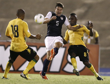 Jun 7, 2013; Kingston, Jamaica; United States player Matthew Besler (5) clears the ball past Jamaica player Jermaine Johnson (8) and Jermaine Hue (18) during their World Cup Qualifying match Friday, June 7, 2013. Mandatory Credit: Winslow Townson-USA TODA