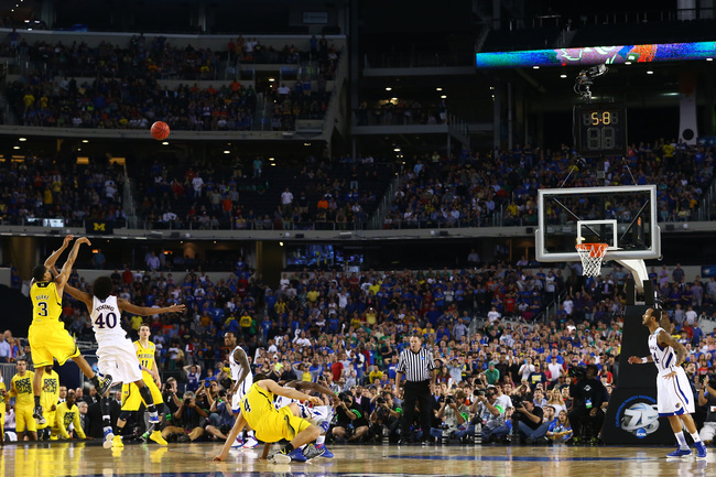 ARLINGTON, TX - MARCH 29:  Trey Burke #3 of the Michigan Wolverines shoots a game tying three pointer in the final seconds of the second half over Kevin Young #40 of the Kansas Jayhawks during the South Regional Semifinal round of the 2013 NCAA Men's Bask