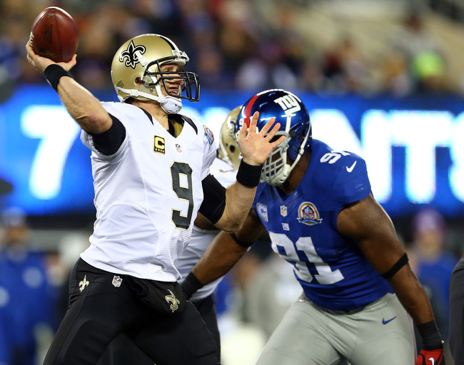 EAST RUTHERFORD, NJ - DECEMBER 09:  Drew Brees #9 of the New Orleans Saints passes under pressure from  Justin Tuck #91 of the New York Giants on December 9, 2012 at MetLife Stadium in East Rutherford, New Jersey.  (Photo by Elsa/Getty Images)
