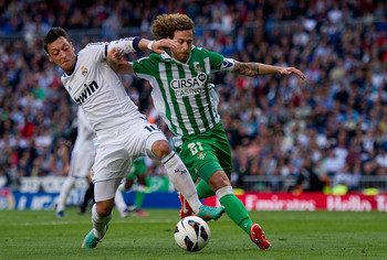 Canas 9right) tussles with Real Madrid's Mesut Ozil
