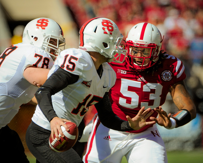 LINCOLN, NE - SEPTEMBER 22: Defensive tackle Thad Randle #53 of the Nebraska Cornhuskers bears down on quarterback Kevin Yost #15 of the Idaho State Bengals during their game at Memorial Stadium on September 22, 2012 in Lincoln, Nebraska. (Photo by Eric F