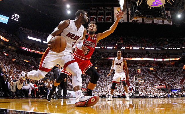 MIAMI, FL - MAY 15: Dwyane Wade #3 of the Miami Heat drives on Marco Belinelli #8 of the Chicago Bulls during Game Five of the Eastern Conference Semifinals of the 2013 NBA Playoffs at American Airlines Arena on May 15, 2013 in Miami, Florida. NOTE TO USE