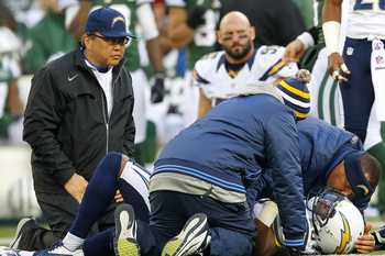 EAST RUTHERFORD, NJ - DECEMBER 23: Brandon Taylor #28 of the San Diego Chargers lies on the ground as team medical personal look after him during the second half against the New York Jets at MetLife Stadium on December 23, 2012 in East Rutherford, New Jer
