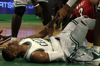 BOSTON, MA - MAY 07:  Kevin Garnett #3 and Ray Allen #20 try to help up teammate Rajon Rondo #9 of the Boston Celtics after he is knocked down by Dwyane Wade #3 of the Miami Heat in Game Three of the Eastern Conference Semifinals in the 2011 NBA Playoffs
