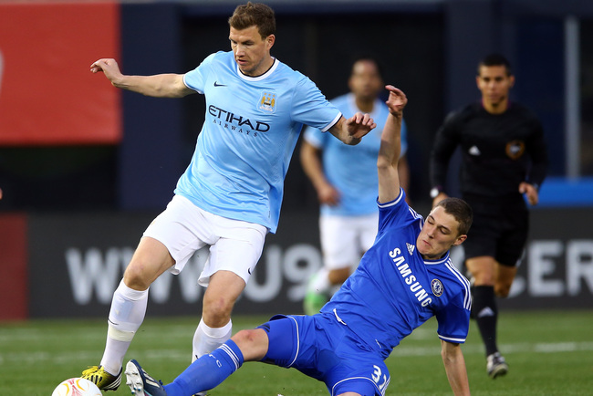 NEW YORK, NY - MAY 25:  Edin Dzeko #10 of Manchester City tries to keep the ball as Andreas Christensen #32 of Chelsea slides at Yankee Stadium on May 25, 2013 in the Bronx borough of New York City. Manchester City defeated Chelsea 5-3.  (Photo by Elsa/Ge