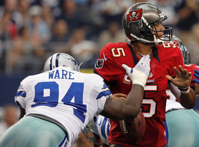 ARLINGTON, TX - SEPTEMBER 23:  Josh Freeman #5 of the Tampa Bay Buccaneers fumbles the ball after being hit by DeMarcus Ware #94 of the Dallas Cowboys at Cowboys Stadium on September 23, 2012 in Arlington, Texas. The Dallas Cowboys beat the Tampa Bay Bucc