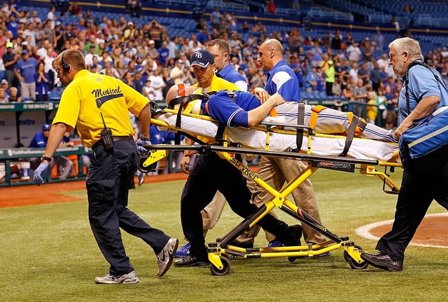 ST. PETERSBURG - MAY 07:  Pitcher J.A. Happ #48 of the Toronto Blue Jays is taken off the field after he was hit by a line drive from the Tampa Bay Rays during the game at Tropicana Field on May 7, 2013 in St. Petersburg, Florida.  (Photo by J. Meric/Gett