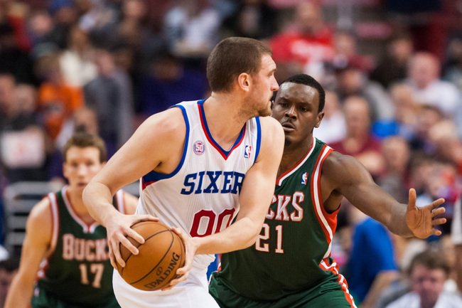 Mar 27, 2013; Philadelphia, PA, USA; Milwaukee Bucks center Samuel Dalembert (21) defends Philadelphia 76ers center Spencer Hawes (00) during the fourth quarter at the Wells Fargo Center. The Sixers defeated the Bucks 100-92. Mandatory Credit: Howard Smit
