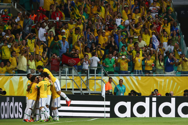 SALVADOR, BRAZIL - JUNE 22:  Neymar of Brazil is mobbed by his team-mates after he scored their second goal from a free kick during the FIFA Confederations Cup Brazil 2013 Group A match between Italy and Brazil at Estadio Octavio Mangabeira (Arena Fonte N