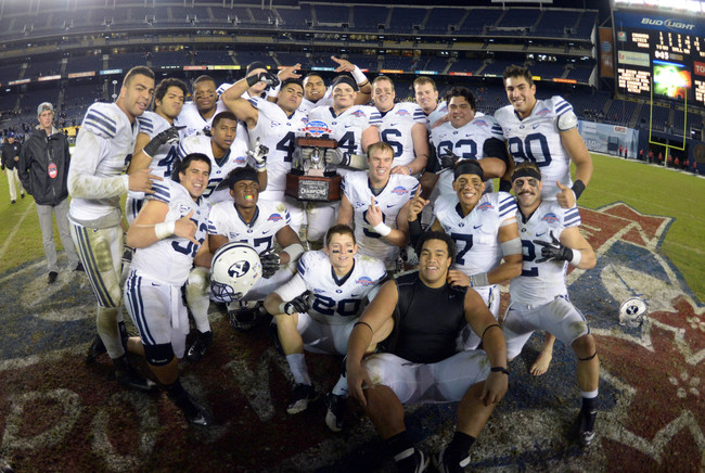 Dec 20, 2012; San Diego, CA, USA; BYU Cougars players pose with the 2012 Poinsettia Bowl trophy after the game against the San Diego State Aztecs at Qualcomm Stadium. BYU defeated San Diego State 23-6. Mandatory Credit: Kirby Lee/Image of Sport-USA TODAY