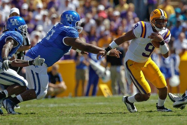 October 1, 2011; Baton Rouge, LA, USA;  LSU Tigers quarterback Jordan Jefferson (9) runs away from Kentucky Wildcats defensive tackle Mister Cobble (97) during the fourth quarter at Tiger Stadium. LSU defeated Kentucky 35-7. Mandatory Credit: Derick E. Hi