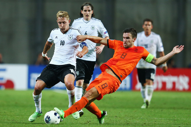 PETAH TIQWA, ISRAEL - JUNE 06: Lewis Holtby (L) of Germany is challenged by Kevin Strootman of Netherlands during the UEFA European Under 21 Championship match between Netherlands and Germany at Ha Moshava Stadium on June 6, 2013 in Petah Tiqwa, Israel.