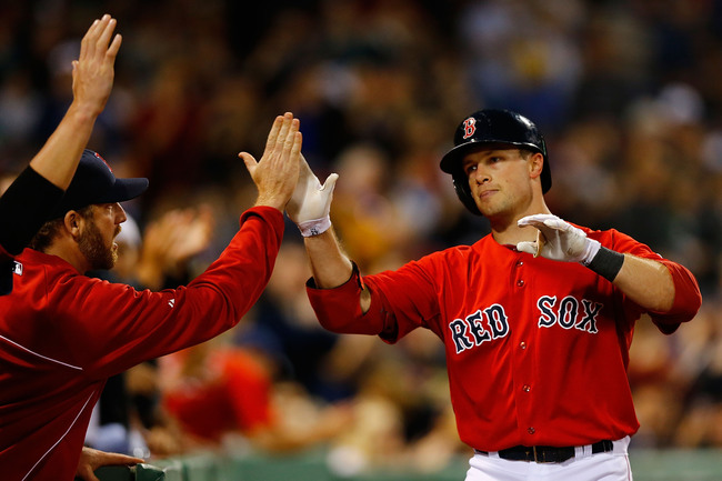 BOSTON, MA - JUNE 18: Daniel Nava #29 of the Boston Red Sox is congratulated by teammates in the dugout after hitting a solo home run in the second inning against the Tampa Bay Rays during the game on June 18, 2013 at Fenway Park in Boston, Massachusetts.